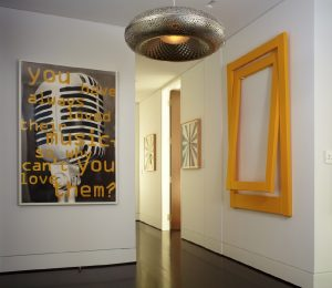 photo of contemporary entryway with large poster, art assemblage and circular overhead light fixture
