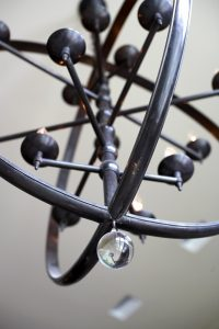 photo of metal sculpted light fixture with glass bead