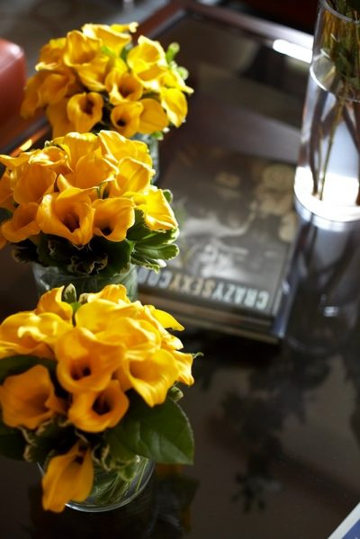 Photo of yellow flowers in vases on coffee table