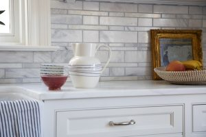 photo of white with gray kitchen counter, cabinets, sink and backsplash