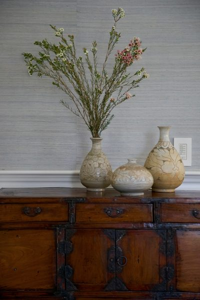 photo of antique sideboard with natural vases