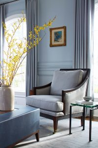 Photo of living room chair with fresh forsythia flowers