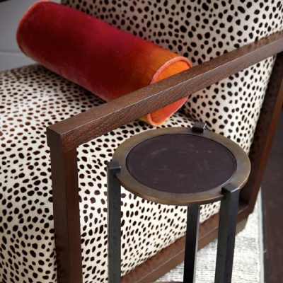 photo of cylinder orange accent pillow on animal print upholstered chair