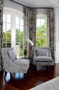 photo of pair of modern upholstered chairs in front of complementary window treatments