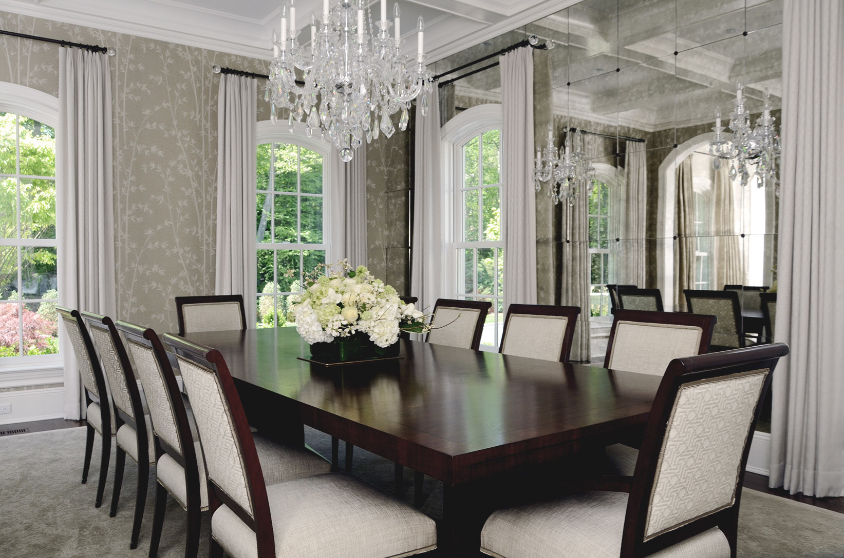 photo of formal dining room with geometric upholstered cream chairs and glass bead chandelier