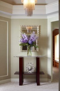 photo of entry way with metal mirror and purple flowers